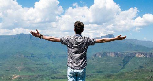 Mann breitet Arme vor weiter Landschaft aus